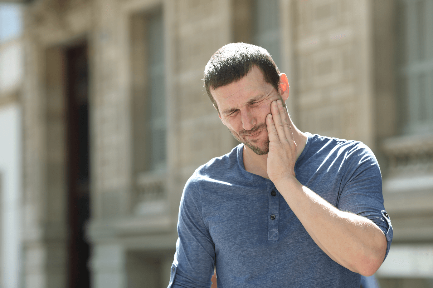 man with TMJ holding his jaw