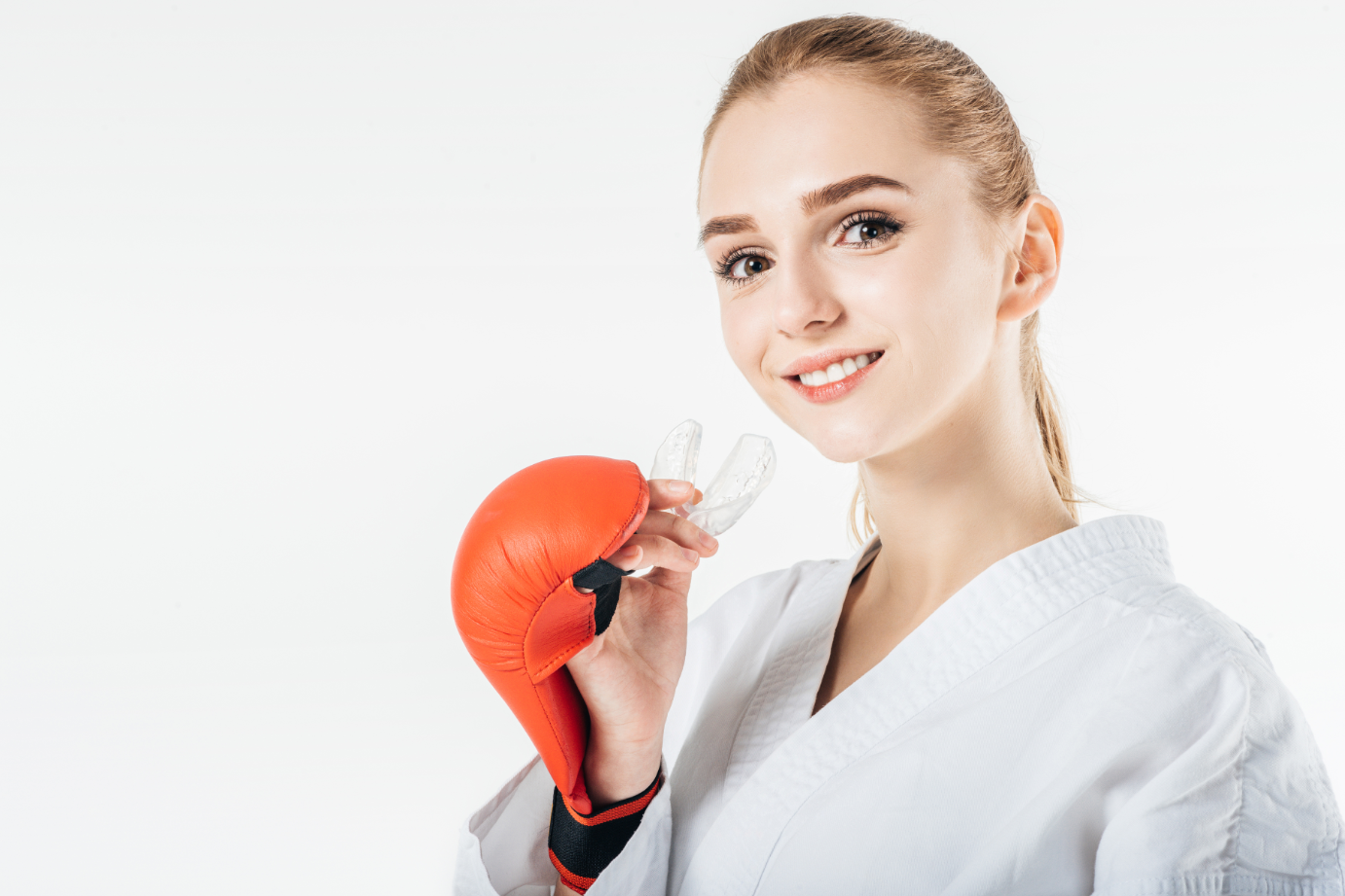 woman wearing boxing gloves and holding an atheletic mouthguard